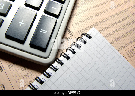 Calculator and notebook laying on financial newspaper. - Stock Photo