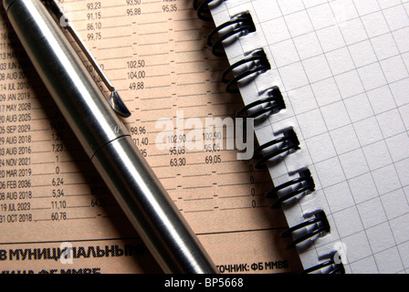 Steel pen and notebook on newspaper close up. Business concept. - Stock Photo