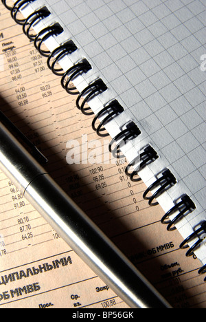 Steel pen and notebook with spiral, laying on newspaper. - Stock Photo