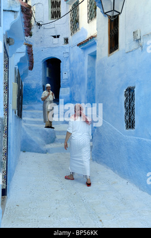 Couple of Moroccan Women or Neighbours Meet & Chat in the Narrow Blue Streets of Chefchaouen, Morocco - Stock Photo