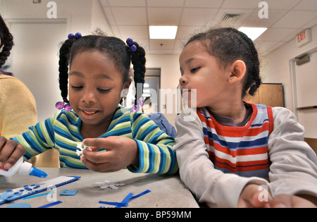 Two children making arts and crafts in a public Library class in CT, United States