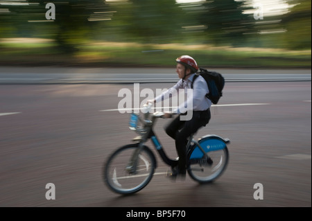 Commuter in London travels through Hyde Park using one of the Cycle Hire Scheme bicycles introduced to London in - Stock Photo