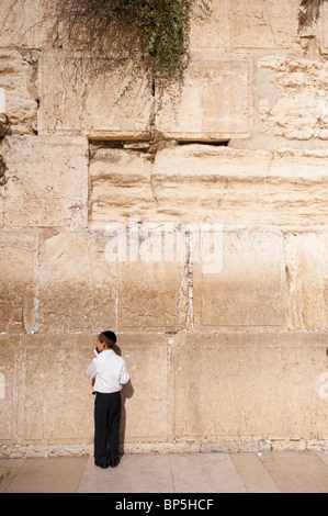 A Jewish boy wearing a kippah kisses a prayer book wile praying at the Western Wall, or Kotel in Jerusalem's Old - Stock Photo