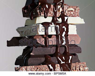 Close up of chocolate syrup dripping over stack of chocolate bars - Stock Photo