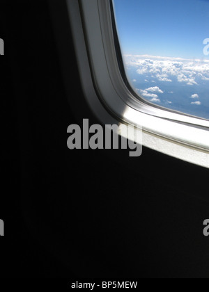 A passenger's view of an airplane's window outside, daylight with blue sky and clouds - Stock Photo
