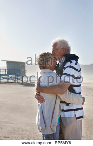 Senior couple hugging and kissing on beach - Stock Photo