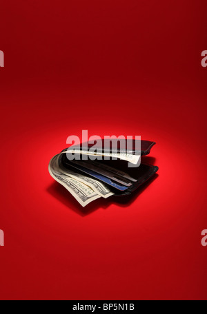 A black leather wallet with money on a bright red background, currency is 300 dollars - Stock Photo