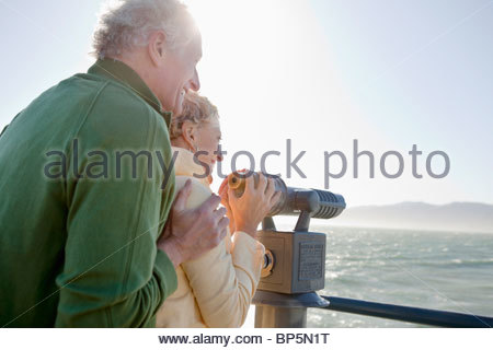 Smiling senior couple looking at ocean with coin-operated binoculars - Stock Photo