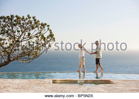Senior couple holding hands along edge of swimming pool overlooking ocean - Stock Photo