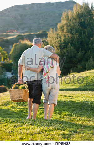 Senior couple hugging and carrying picnic basket on grass - Stock Photo