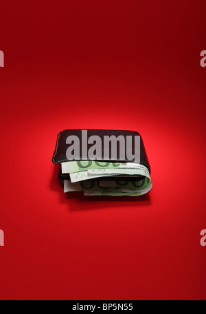 A black leather wallet with money on a bright red background, currency is 300 Euros - Stock Photo