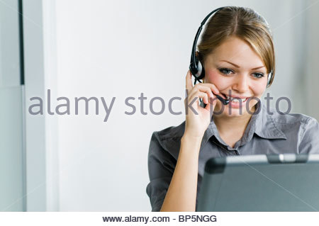 Smiling businesswoman wearing headset and using laptop in office - Stock Photo