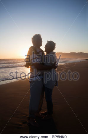 Senior couple hugging on beach at sunset - Stock Photo