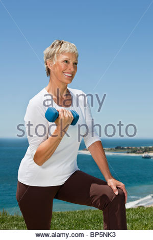 Senior woman doing biceps curls with dumbbell - Stock Photo