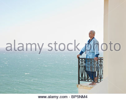 Senior man in bathrobe on balcony overlooking ocean - Stock Photo