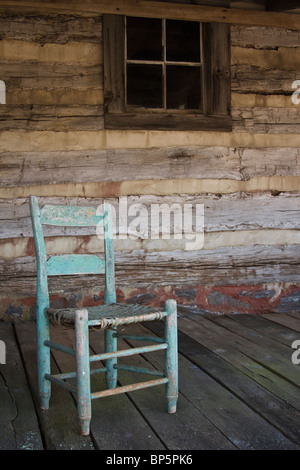 Old Antique Rocking Chair On Wooden Deck Of Log Cabin - Stock Photo