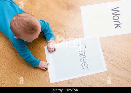 Baby with papers saying work and career - Stock Photo