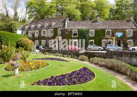 The Swan Hotel set beside the River Coln in the Cotswold village of Bibury, Gloucestershire - Stock Photo