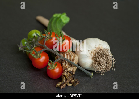 A selection of fresh organic garden vegetables including garlic courgette and tomato - Stock Photo
