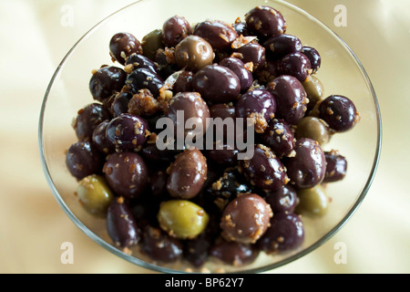 Olives in a bowl on a yellow table cloth - Stock Photo