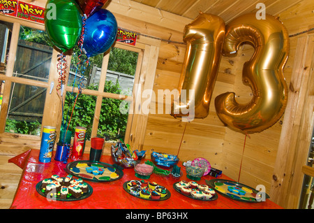 Horizontal close up of a table of party food laid out for a child's 13th birthday party. - Stock Photo