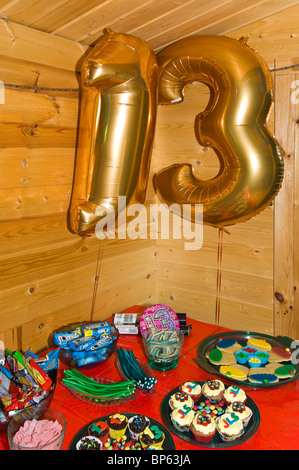Vertical close up of a table of party food laid out for a child's 13th birthday party. - Stock Photo