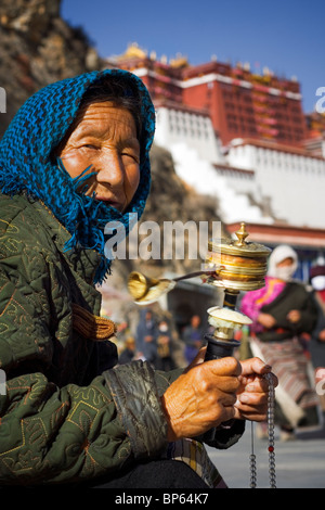 An elderly woman in traditional head dress spins her prayer wheel in front of the Potala palace, Lhasa, Tibet, China. - Stock Photo