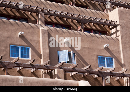 Three windows and many vigas casting shadows on a building in the Pueblo revival style architecture in Santa Fe, - Stock Photo