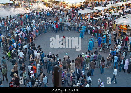 Berber musicians and dancers gathering a crowd in the central market square of Jemaa El Fna in Marrakech - Stock Photo