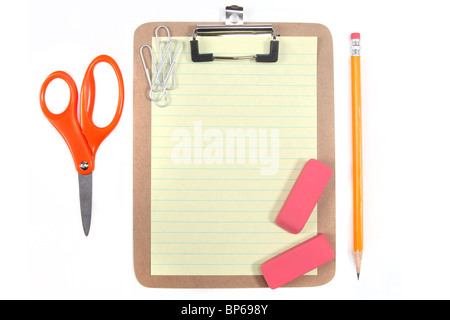 Clipboard With Yellow Lined Paper and School Office Supplies on a White Background - Stock Photo