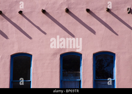 Vigas casting shadows over three windows of a building in the Pueblo revival style of architecture in Santa Fe, - Stock Photo