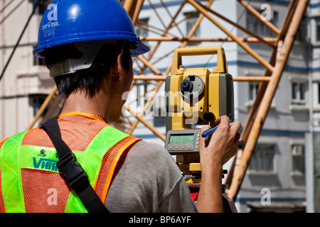 An engineer taking readings off a theodolite on a construction site in Hong Kong. - Stock Photo