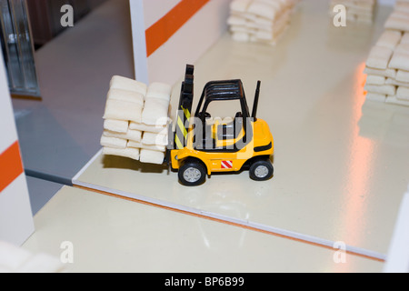 The forklift truck loader cargo in a toy warehouse. - Stock Photo