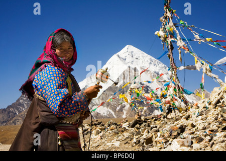 A Tibetan pilgrim spins her mani prayer wheel on the Mila mountain pass (5300m) - Stock Photo