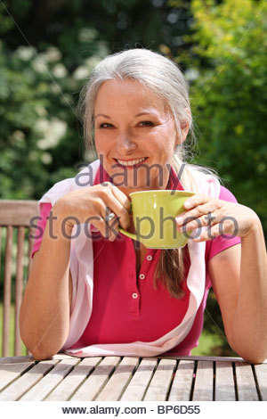 older woman relaxing in garden drinking a cup of coffee - Stock Photo