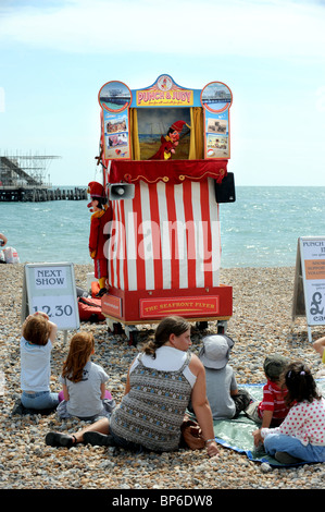 Kids and parents watch a Punch and Judy show on Worthing beach - Stock Photo
