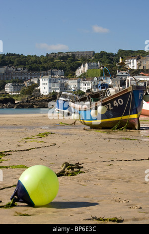 A yellow buoy in front of beached fishing boats in St Ives harbour at low tide. - Stock Photo