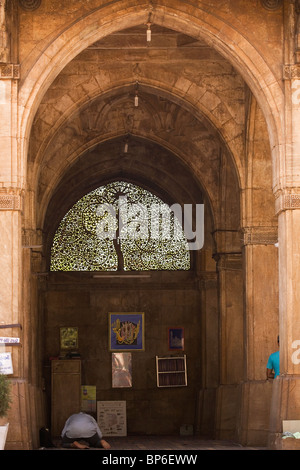 A man prays in front of the famous Jali work of the screen in the Sidi Saiyyed Mosque in Ahmedabad, Gujarat, India. - Stock Photo