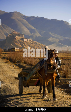 A tibetan man rides his horse away from the Dzong/Fortress of Gyantse in Gyantse, Tibet - Stock Photo