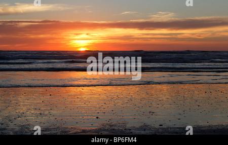 A sunset over Ninety Mile Beach, New Zealand - Stock Photo