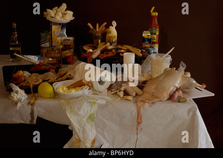 A table with a grill and an excess of various grilling meats and barbecue foods, still life - Stock Photo