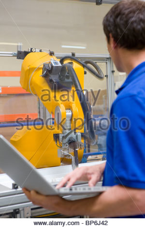Worker watching robotic arm working on assembly line in factory - Stock Photo