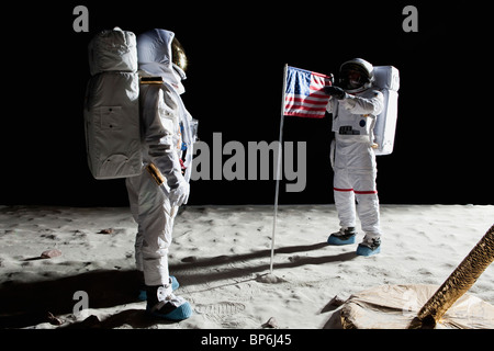 Two astronauts on the moon, an American flag in between them - Stock Photo
