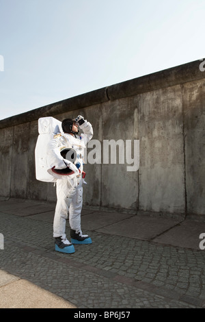 An astronaut on a city sidewalk looking up into the sky - Stock Photo