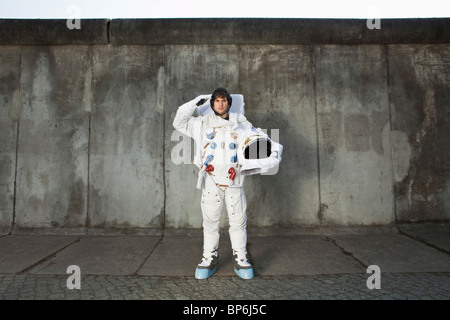 A saluting astronaut standing on a sidewalk in a city - Stock Photo