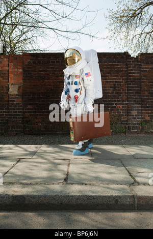An astronaut carrying a suitcase and walking on a city sidewalk - Stock Photo