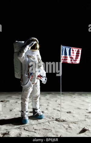 An astronaut on the surface of the moon saluting an American flag - Stock Photo