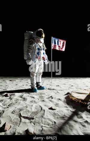 An astronaut on the moon standing next to an American flag - Stock Photo