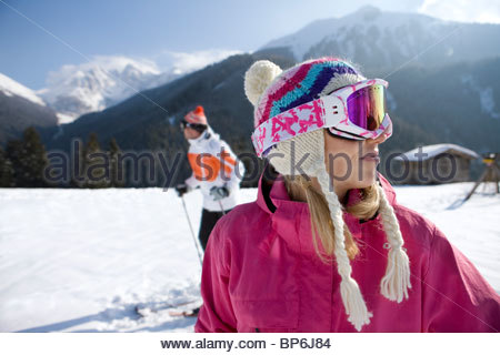 Woman standing in snow  with mountains in background - Stock Photo
