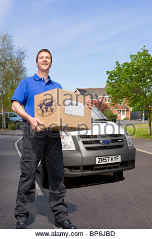 Delivery man delivering cardboard box - Stock Photo